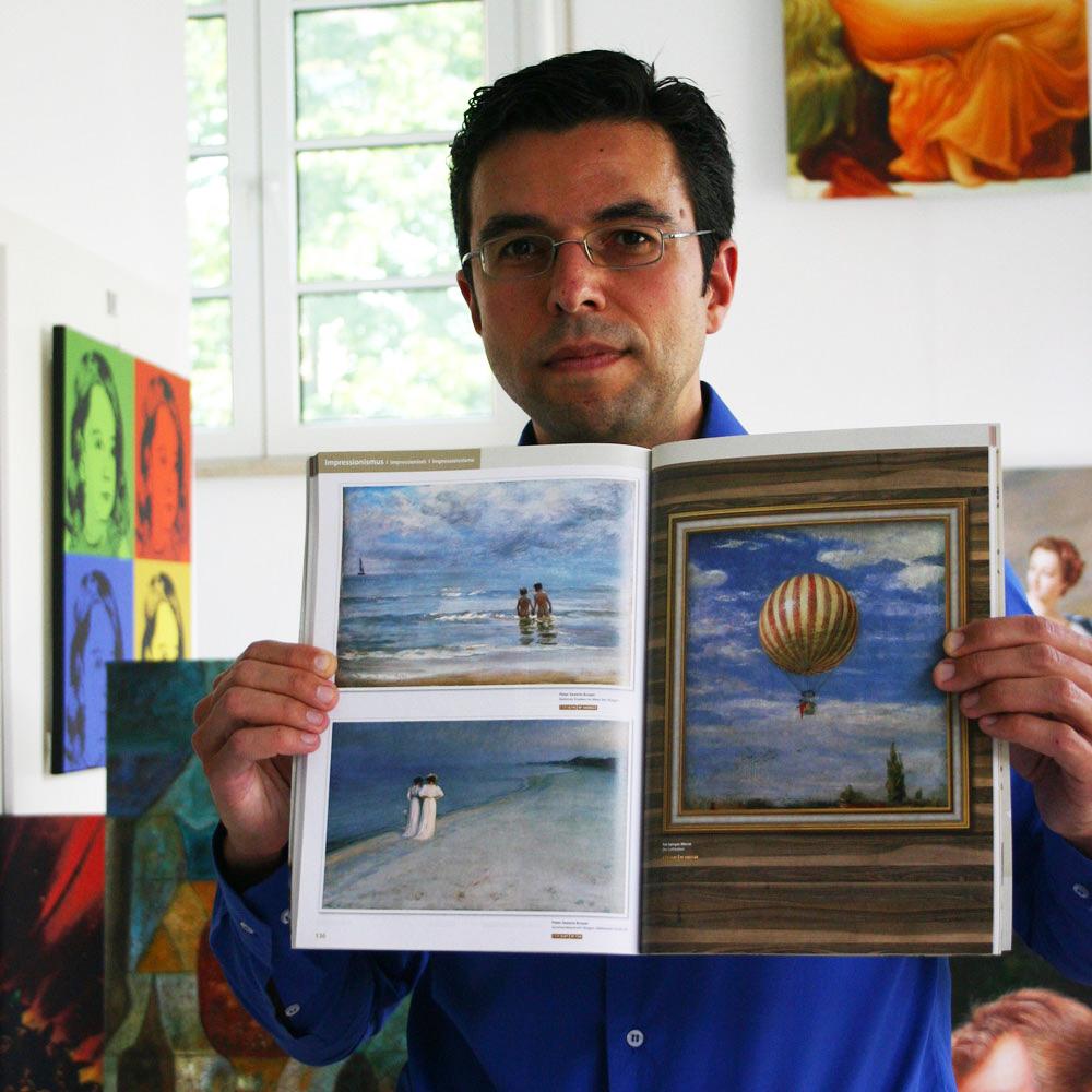 Inhaber Daniel Cid Gomez mit einem Kunstkatalog mit bestimmten Farben